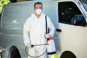 Pest control worker beside his van