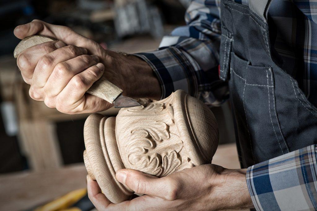 Man engraving designs on wood