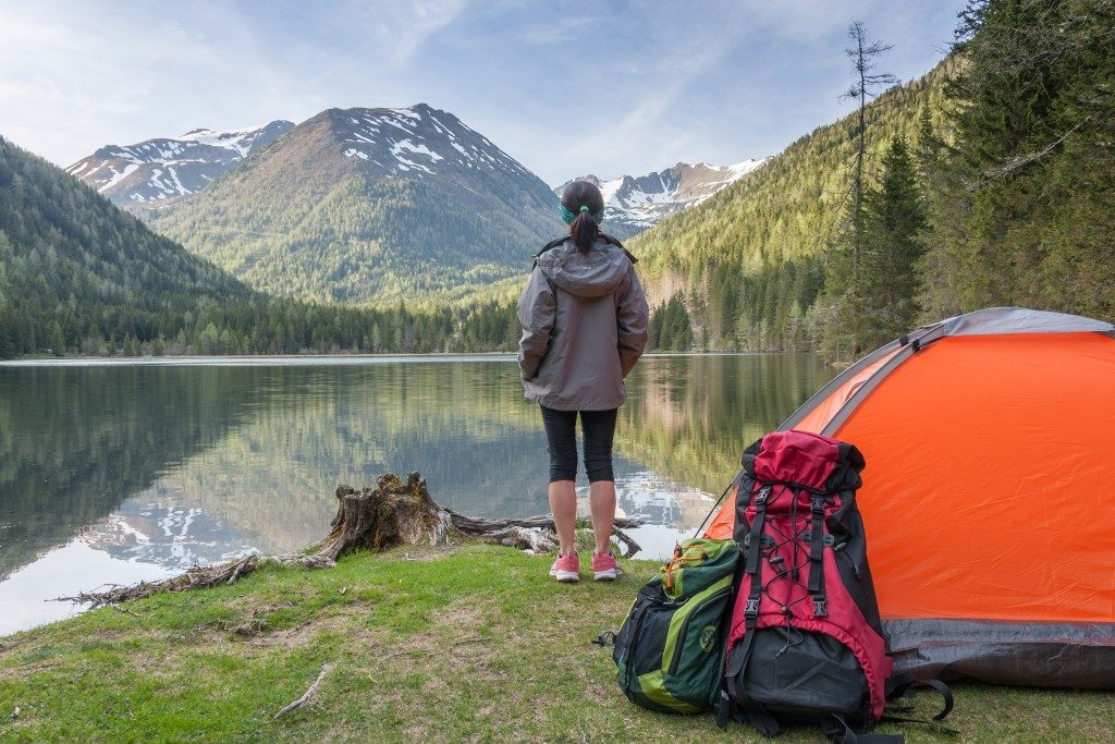 Woman camping in front of a lake